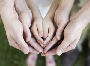 Hands of a family coming around each other to support one another