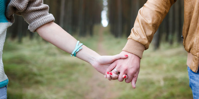 Couple holding hands walking through forest