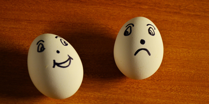 Happy and sad face painted on eggs