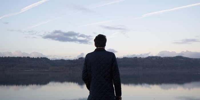 Man standing looking over glassy lake