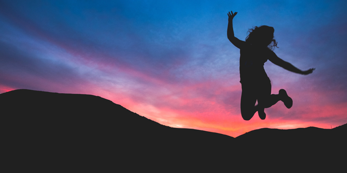 Silhouette of woman jumping for joy