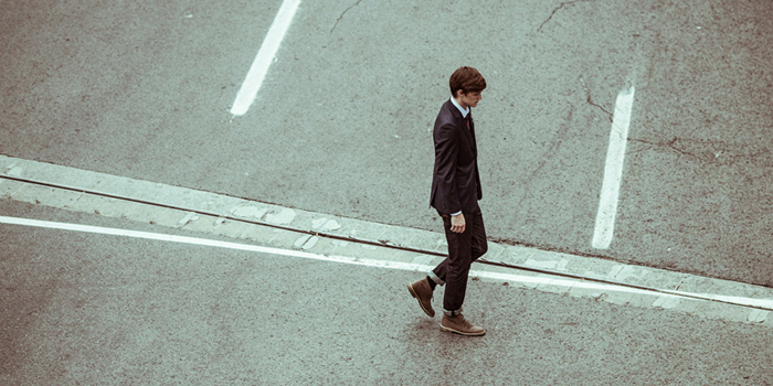 Man walking down road looking tired