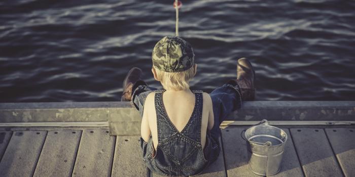 Child on the edge of dock fishing