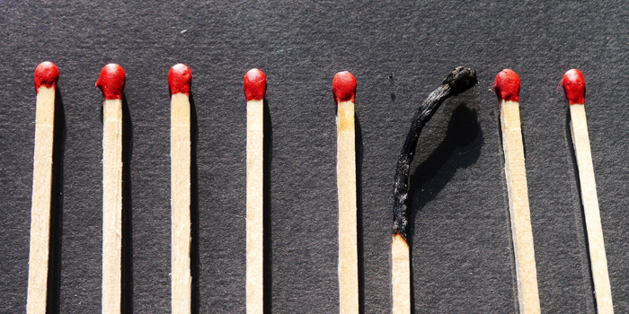 Line of matches with one match burned out