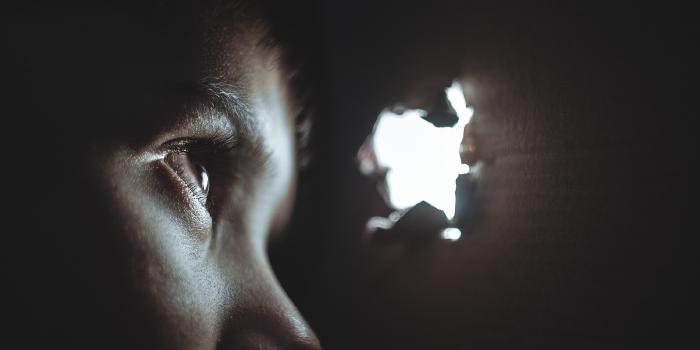 Boy looking through an open hole in a cardboard box
