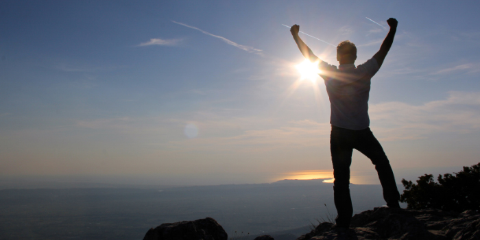 Man with his hands raised in the air in victory and accomplishment