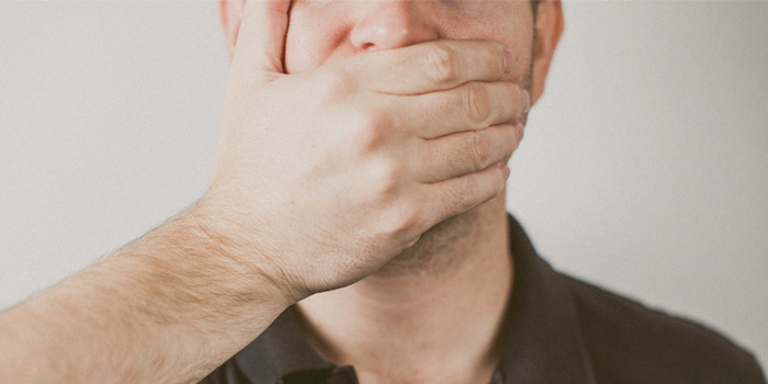 Man being silent with hand over his mouth