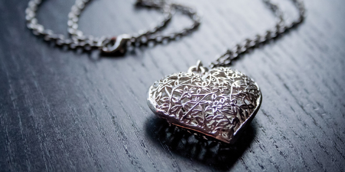 Valuable silver heart necklace laying on a table