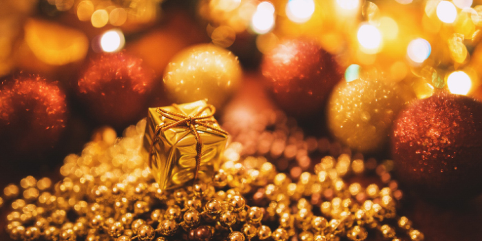 Gold present surrounded by Christmas ornaments