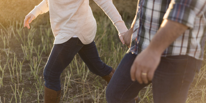 Husband and wife walking together through a field