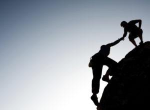Man helping other man climb mountain