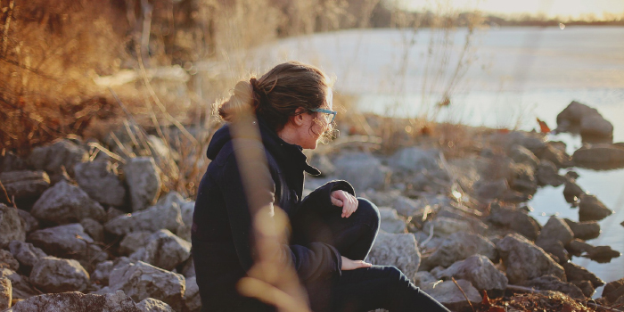 Woman sitting alone on rocks next to a lake