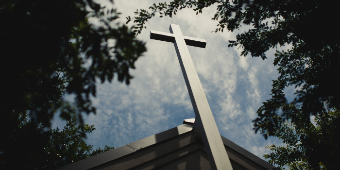 Cross on a church steeple bordered by trees