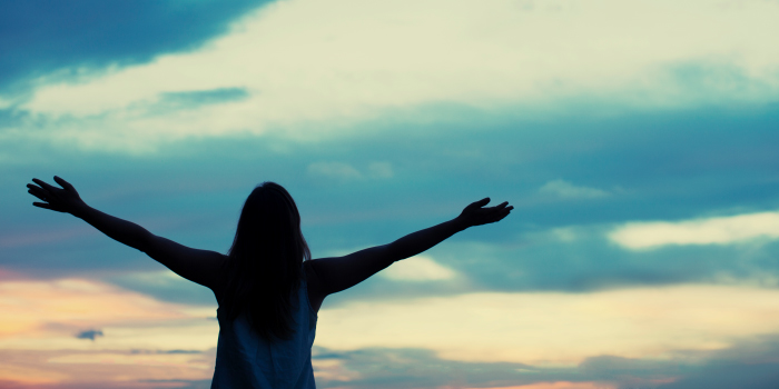 Silhouette of a woman lifting her hands up to the sky