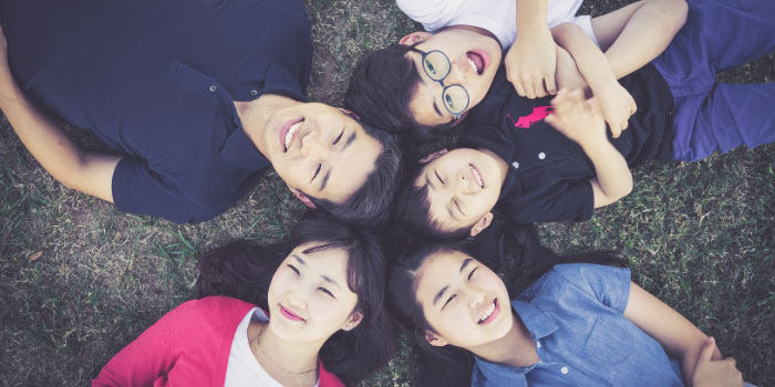 Asian family of 5 laying down in the grass