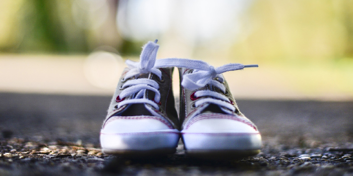 Pair of empty baby shoes sitting on the asphalt