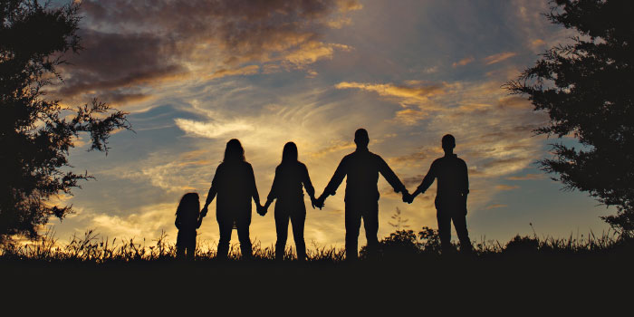 Silhouette of a family standing outdoors holding hands
