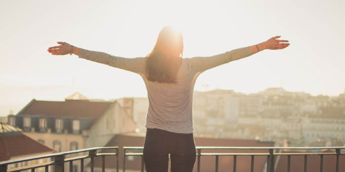 Woman standing on a balcony in the sun with her hands up in the air