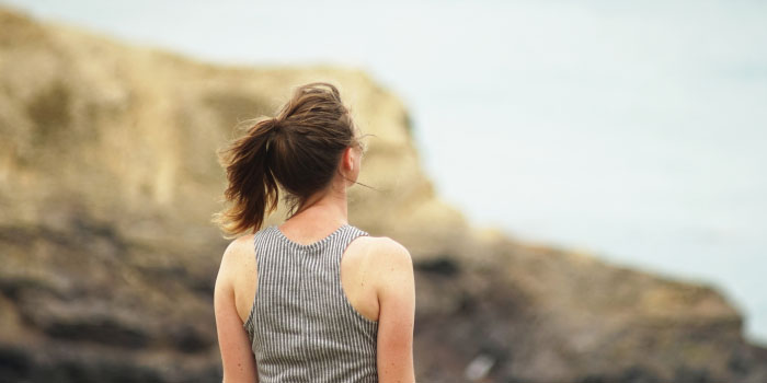 Woman standing on a cliff side looking out