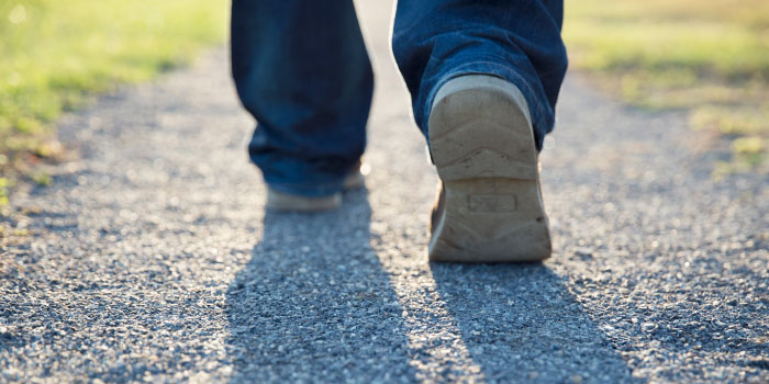 closeup on feet of a man walking down a path