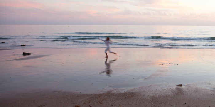 Woman running down a sunset beach