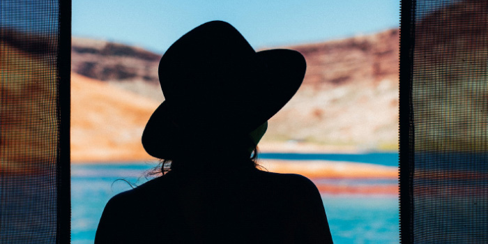 Silhouette of a woman in a hat looking out into the sunlight