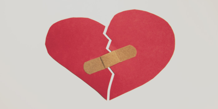 Broken paper heart with a bandage over it