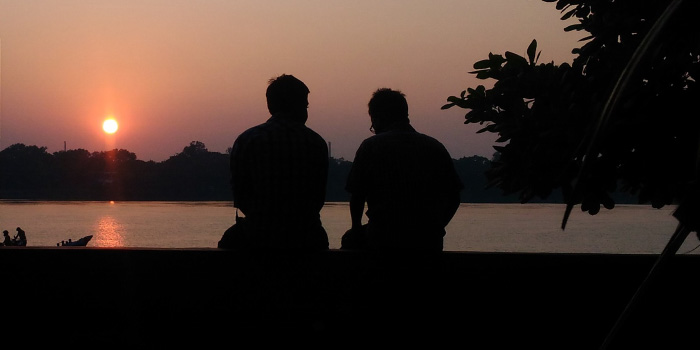 Two friends sitting next to each other talking at sunset