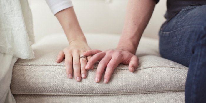 Married couple sitting on the couch touching hands