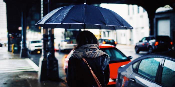 Woman walking under an umbrella in the rain