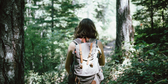 Woman with a backpack hiking through woods