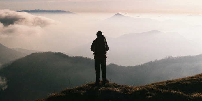 Silhouette of man staring out over mountain valley