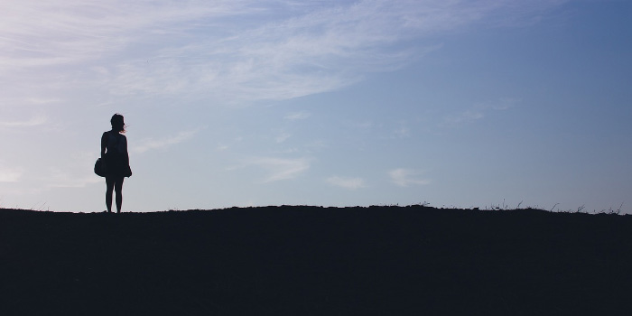 Silhouette of a woman standing on a hill looking away
