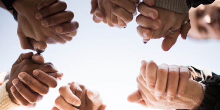 Group of people holding hands to pray