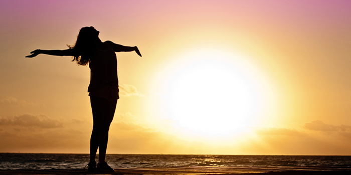 Woman standing in sunlight with hands in the air