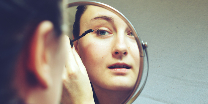 Woman putting on makeup in the mirror