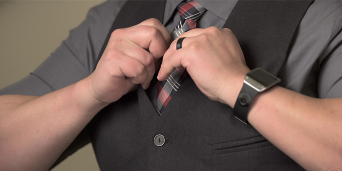 Man putting on tie