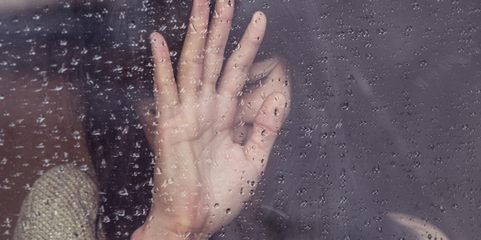 Woman crying next to window