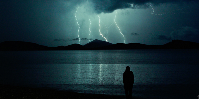 Person standing near to lightning storm