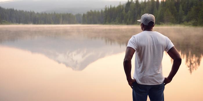 Man standing by glassy lake