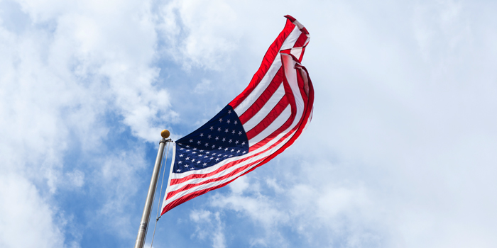 American flag against cloudy sky