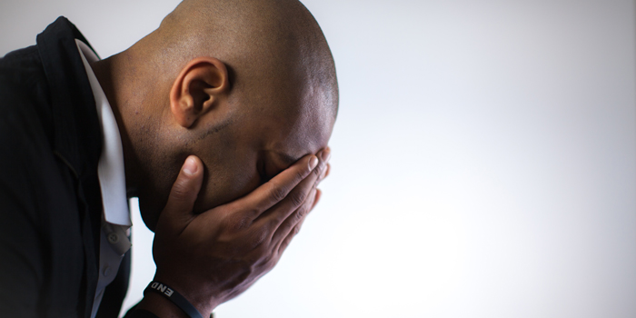 Man with hands covering his face