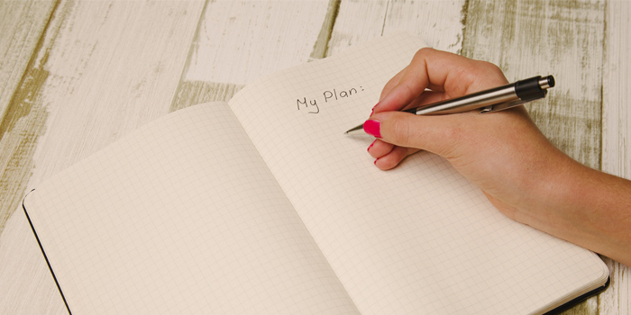Woman writing out her plans on paper