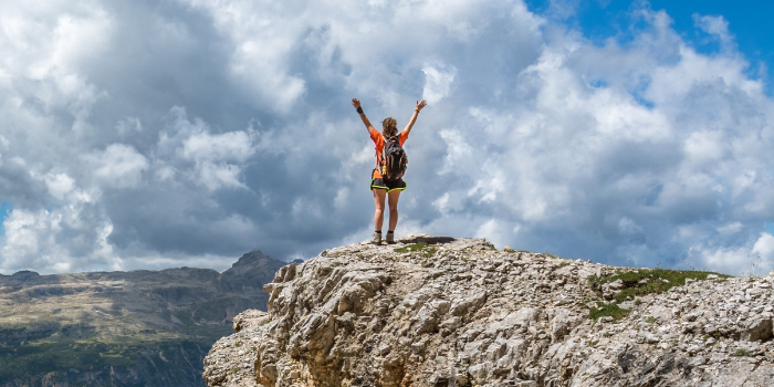 Woman standing on top of a mountain with her hands up in the air in achievement