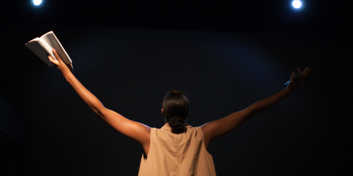 Woman standing on stage with her hands up in the air in surrender