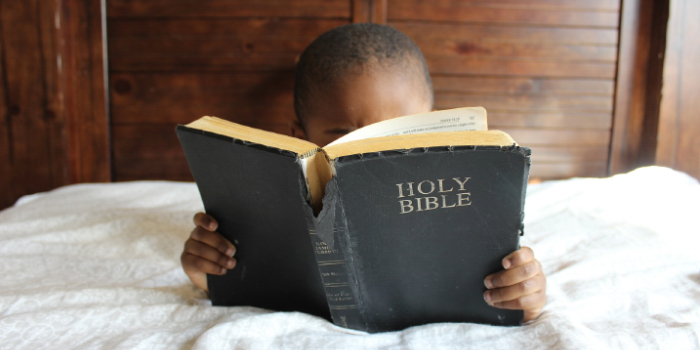 Boy laying on bed reading a bible