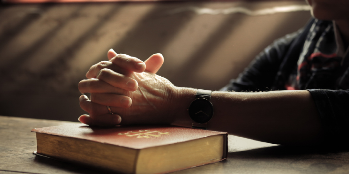 Woman praying with her hands folded on top of a bible