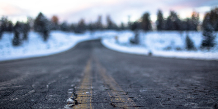 Cracked road surrounded by snow