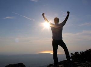 Man standing in victory on a mountaintop