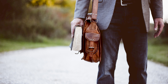 Man walking away with a bag and a Bible in hand